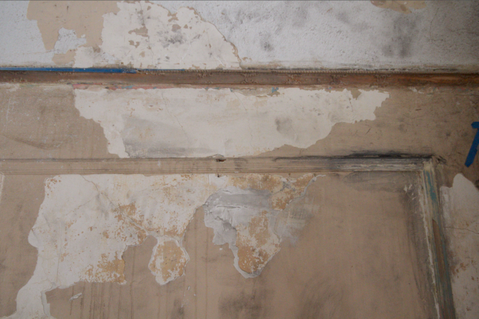 Damaged plaster, filth from the ceiling demo, and splotches of paint stripper.
